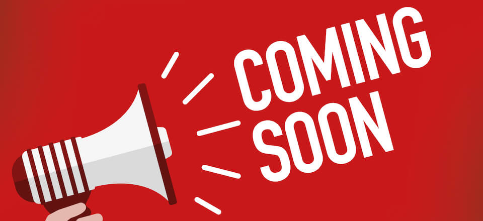 """A red image showing a stylized megaphone shouting the words """"Coming Soon"""""""
